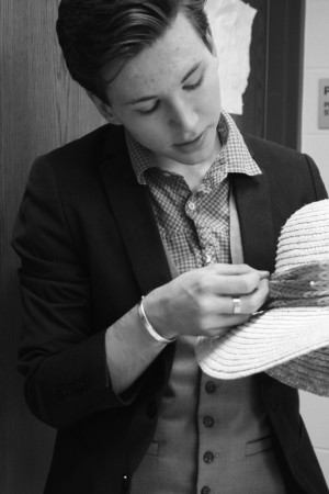 Patrick Broderick, senior and costumes co-captain, work to add a piece of fabric to a hat.