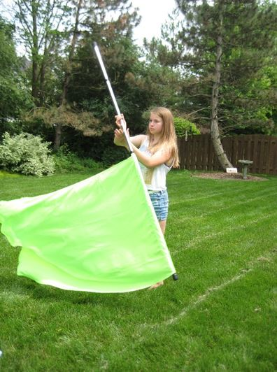 Abby Smith, freshman, practices with her guard flag. She joined Color Guard with hopes to meet lots of new friends. Photo credits to Abby Smith.