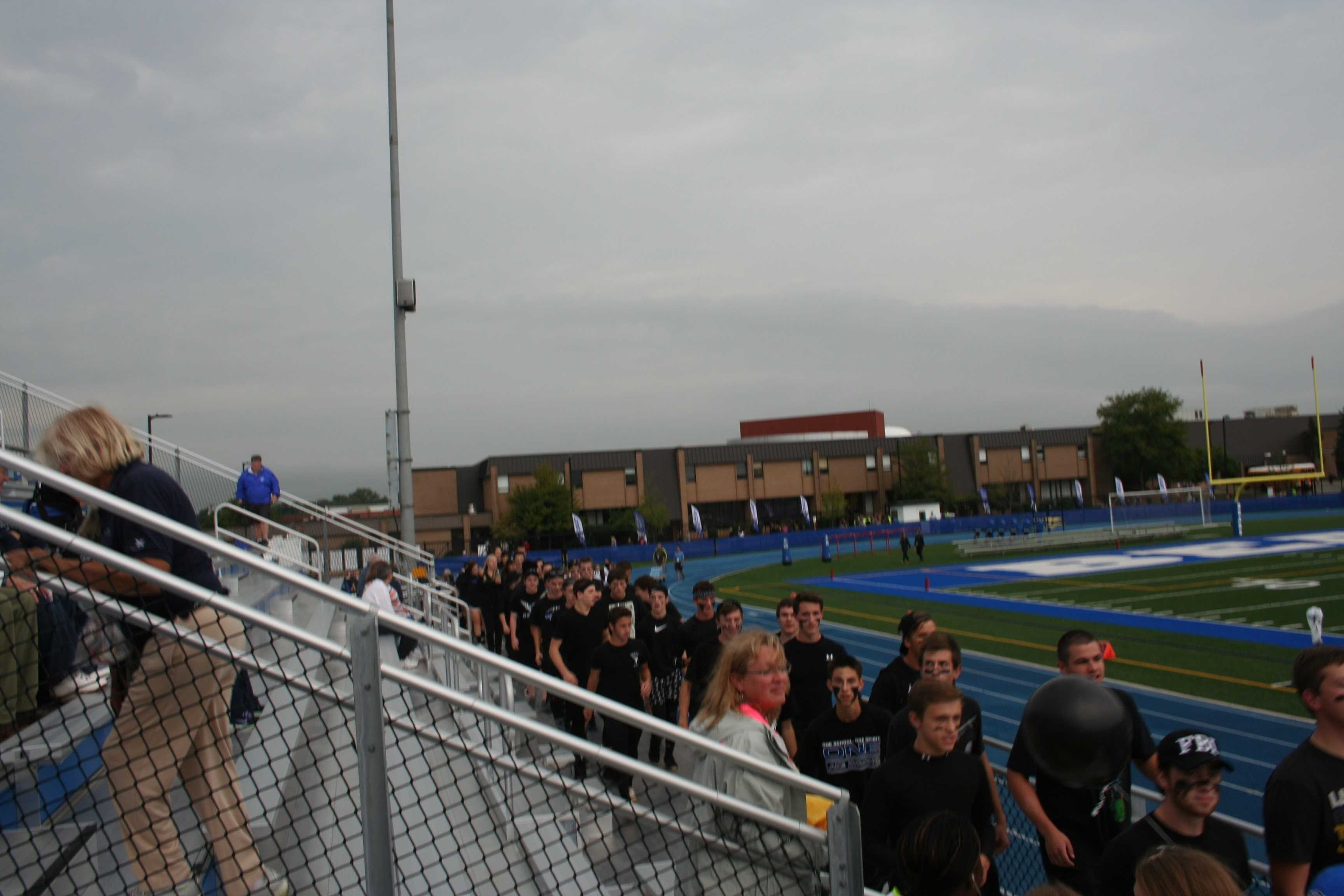 Students march from inside the school into the stands, lead by their section leader, Noah McGarr, senior.