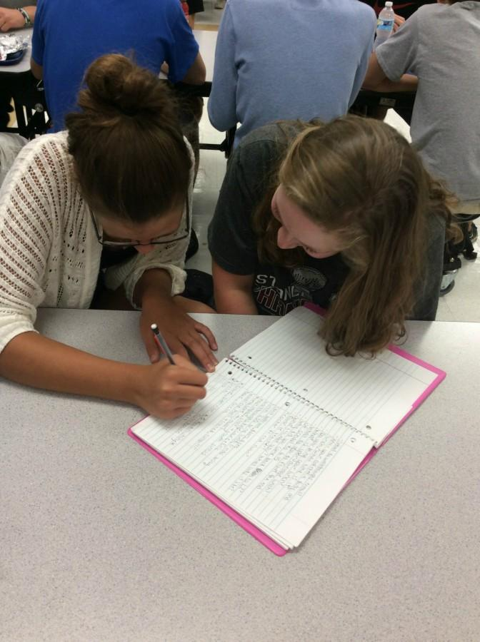 Alyson Wisnionski, freshman, and Jessica Mueller, freshman, hand write their notes rather than using their iPads. Studies show taking longhand notes help students remember the content more than if they use their laptops.