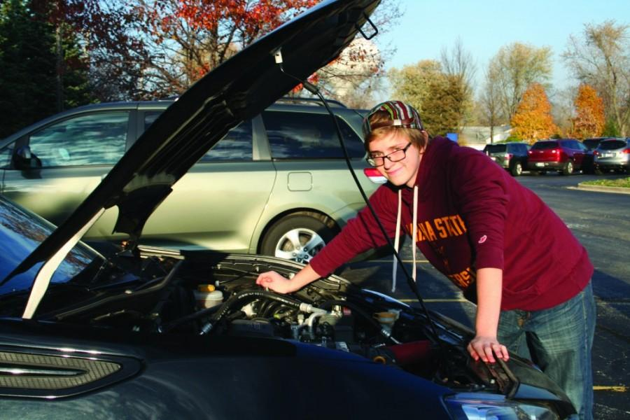Mike Young, senior, works on his car to practice his skills as a car mechanic. Young is one of many who have decided to graduate early, and is planning to use this time to work.