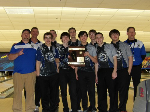 Coaches, Mike Sutton, Kirk Reusch, and Steve Schmitz gather with the boys bowling team as they pose with their first place plaque at regionals. This is the teams first time winning the IHSA regional championship.