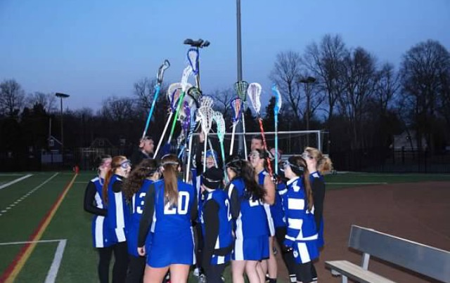 Junior Varsity girl's lacrosse team embraces each other with their sticks held high