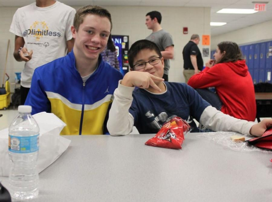 Brett Hensely, junior, sits with David Bae, sophomore, during sixth period lunch as part of the Lunch Buddies program. The program was started to integrate Life Skills students with athletes.  Photo by Jemma Kim