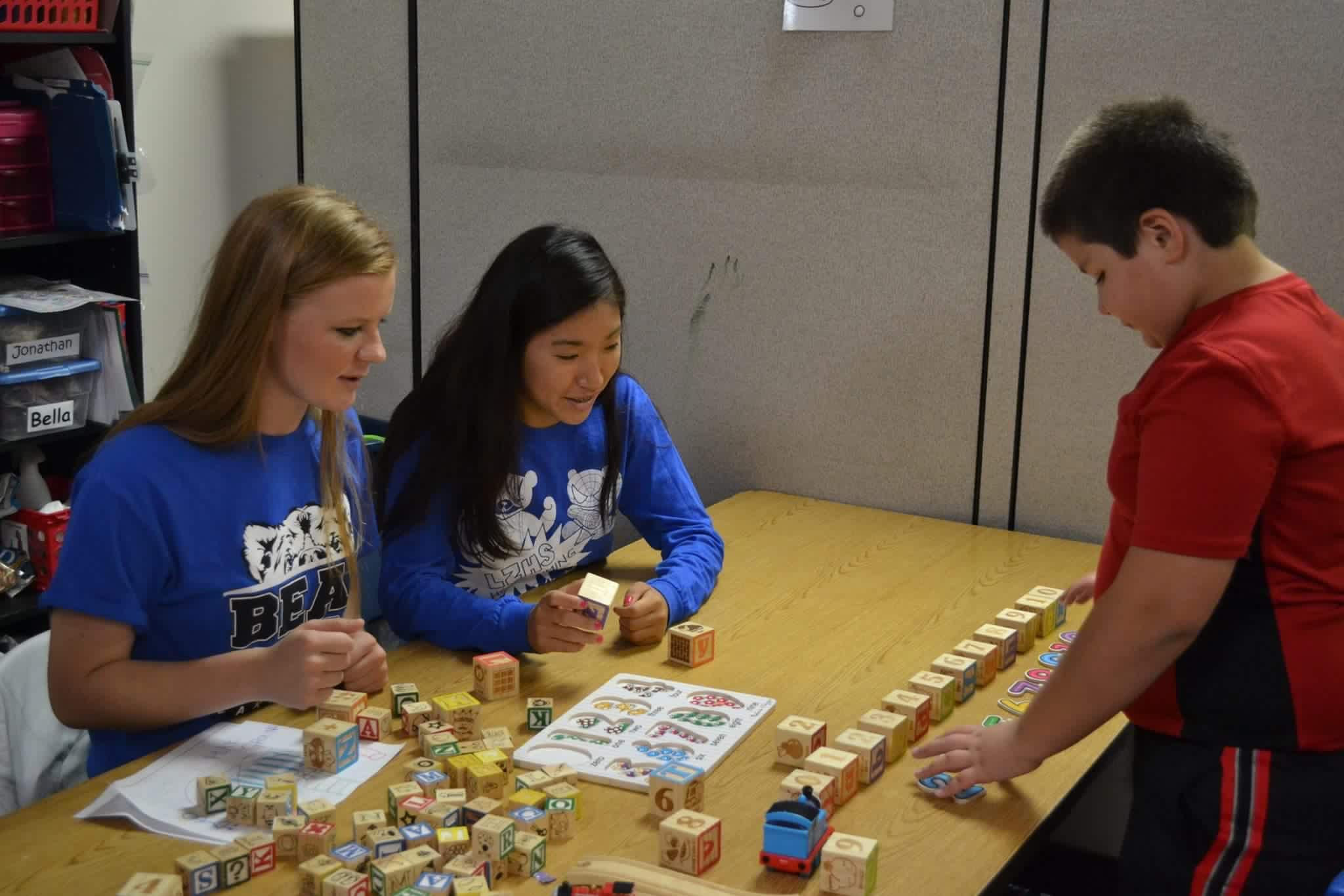 Emma Wenckowski, junior and 16-17' Student Council president, helps students at the Alexander Leigh Center for Autism with Jemma Kim, junior and 16-17' Student Council Vice President. The entire club visited the ALCA to learn about this years charity for charity bash.