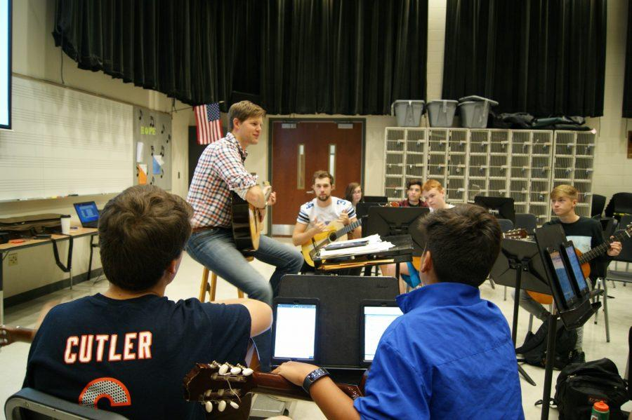 Nathan Sackschewsky, orchestra director and guitar teacher, plays along with his students.