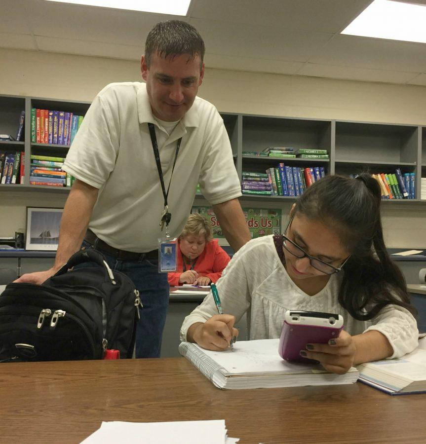 Josh Johns,  math aide, assists Alena Naqvi, senior, during an open period. Johns has been an MRC aide for two years after being a substitute for various math and science classes.