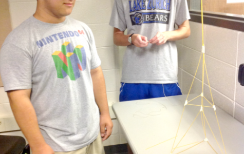 Andy Gatza, freshman, and John Burke, senior, finish a tower their group made out of spaghetti, tape, and a marshmallow. This exercise on the first day of class was designed to promote problem solving and creativity, according to Ann Heltzel, computer science teacher.