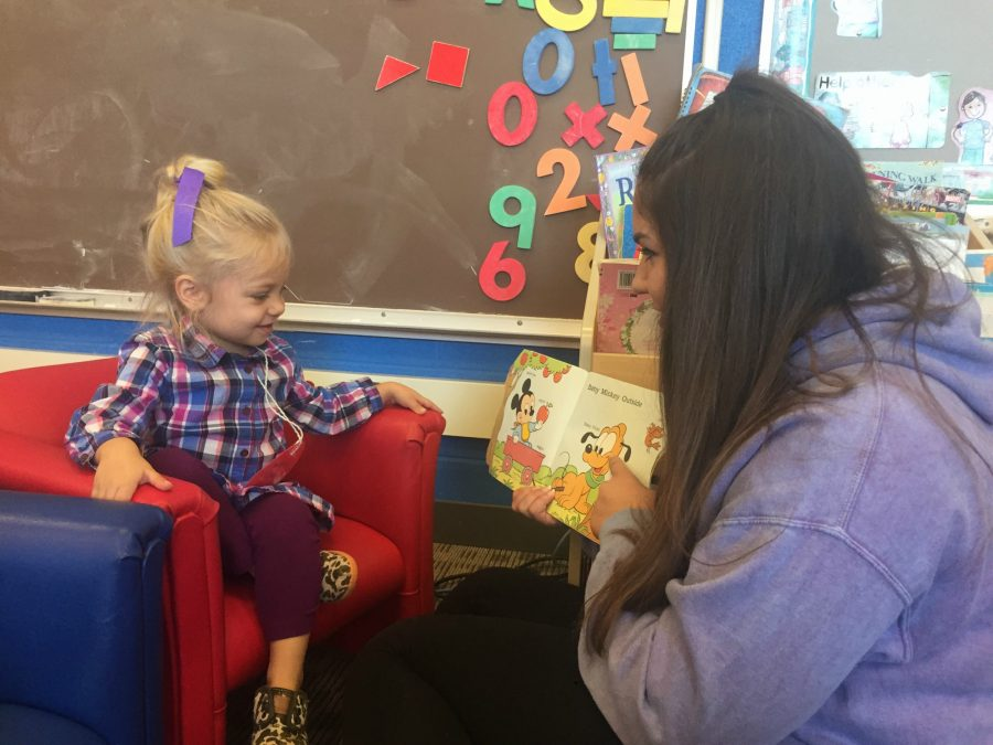 Apollonia Jacobs, preschooler in the child development program, sits and reads with Sydney Shadrick, senior. Jacobs will be aired on TV in a Hillary Clinton commercial.