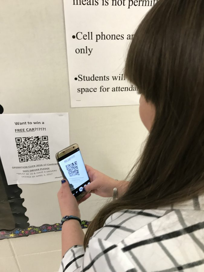 Sarah Shapero, senior, takes a picture of one of the many barcodes on the walls around the school that will take her to where she can sign up for a contest to win a car. She smiles in excitement with the idea of winning a new ride.
