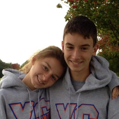 Patrick and Emily Burns stand together in their cross country sweatshirts at the IESA State Championship in 2013.
