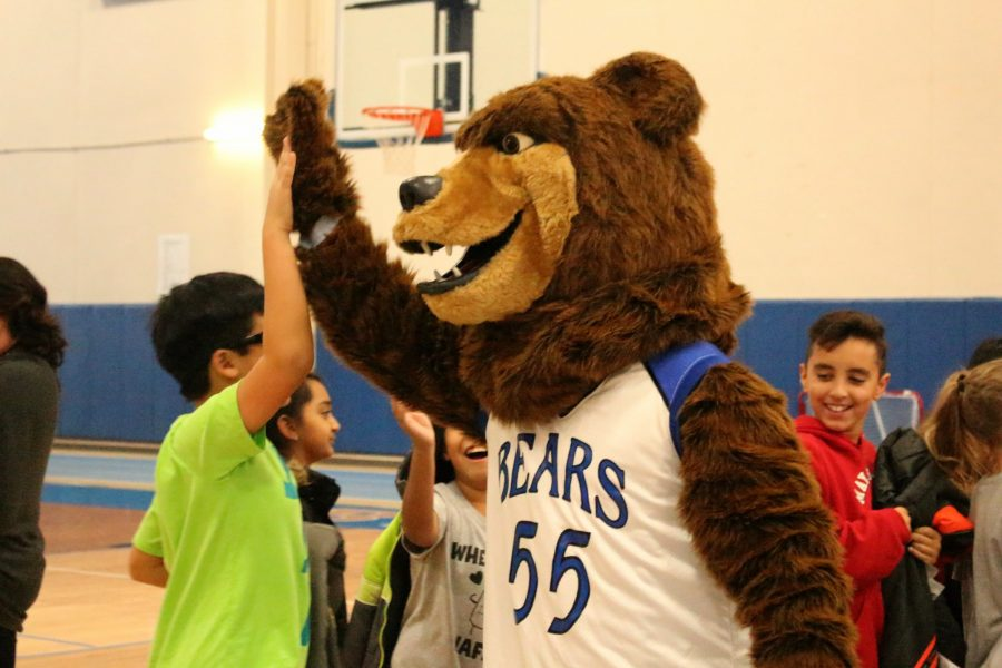 The bear mascot high fives students as they enter the bleachers after being greeted by the band.