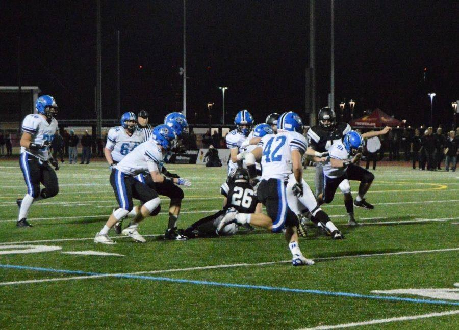 Football players run a play during the November 5 playoff game against Fenwick, a week after alleged hazing took place in the locker room. In response to that incident, administration has reiterated rules on student supervision to faculty and the student body.