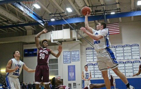 Peter DiCerbo, junior power forward, leaps up for a layup against a Zion Benton defender during Pack the Place.
