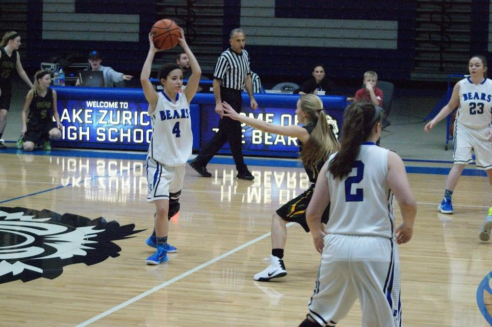 Eleni Papastratakos, junior basketball player, looks for a pass in the November 23 game against Fremd. Papastratakos believes that the gender inequality in attendance at high school sporting events can be corrected.