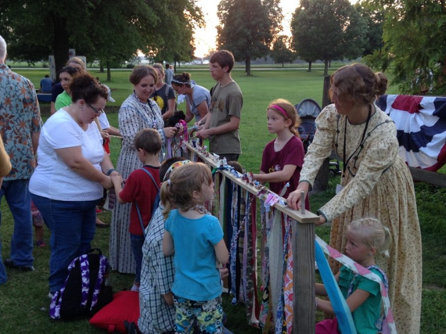 Children participating in the Nauvoo fair weave the rag ties, one of the toys Nathan Holbrook, junior, is making for his Eagle Scout project.