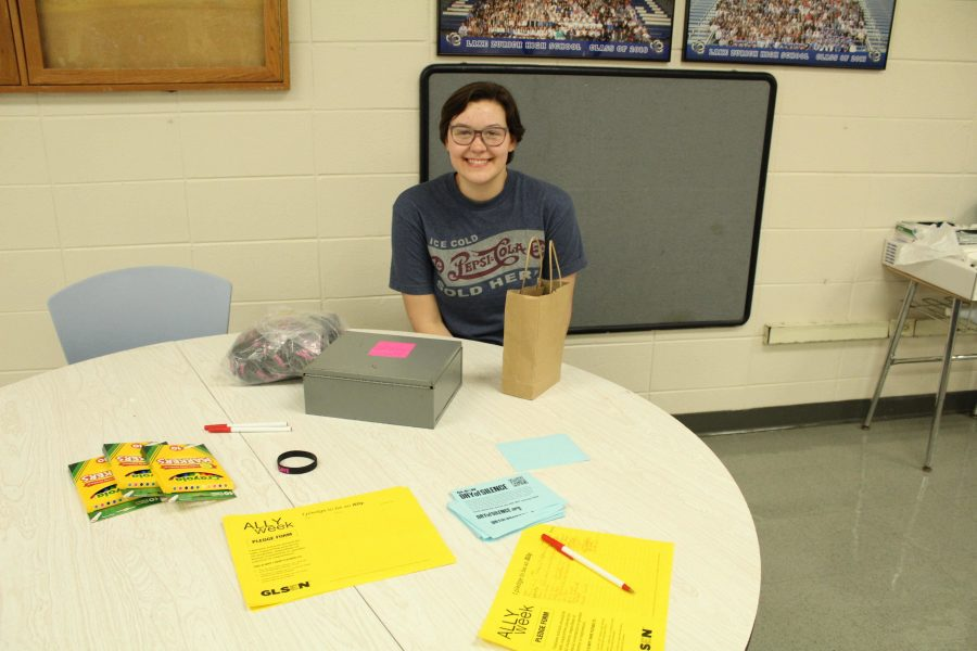 Riley Danca, junior, works at the  Day of Silence informational table to accept pledges of silence.