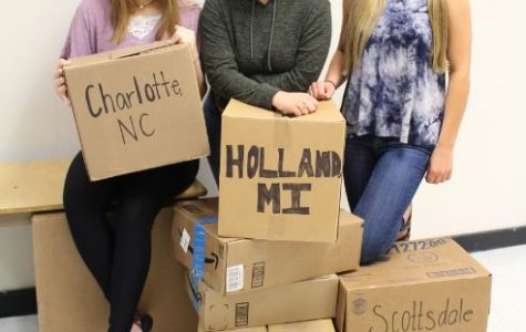 (left to right) Sarah Blase, Vada Murray, and Brianna Reitsch hold moving boxes with their new destination written on them. Those seniors will be moving the summer after graduation.