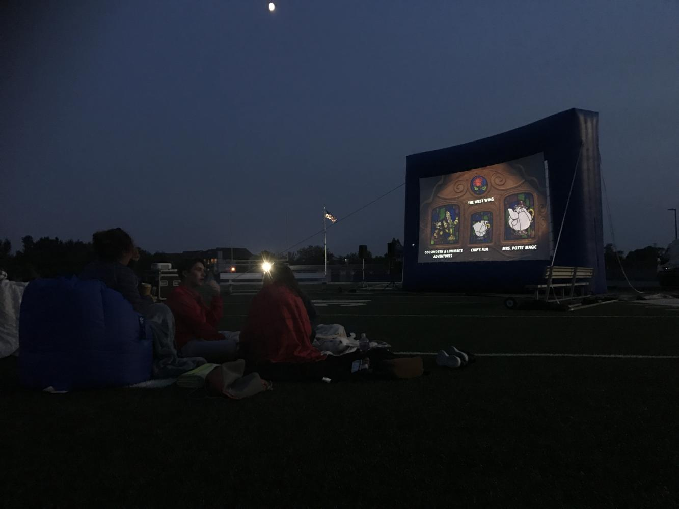 Onlookers watch as Monsters Inc plays on the big screen. Student Council held a showing of the movie on the football field for the annual movie night.