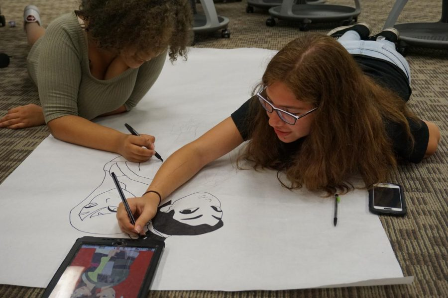 Printy Jordan (left) and Fernanda Del-Vosque (right), both freshmen members of Spectrum, sketch out a poster for the hallway.  Spectrum chose Mulan to match the homecoming this year.