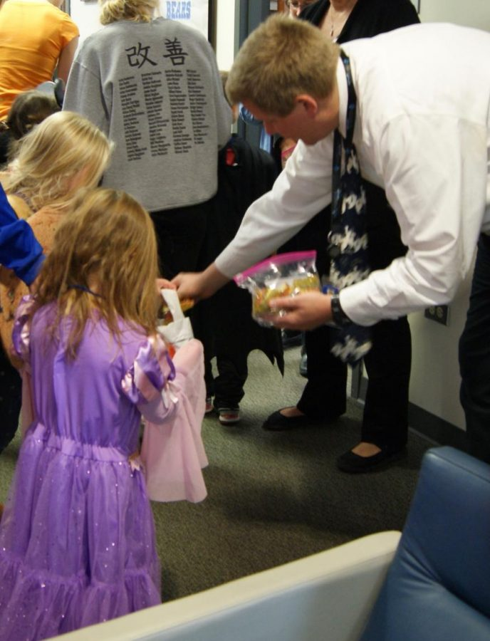 Bo Vossel, principal, places candy in the baskets of the preschoolers after they performed their Halloween song for faculty members in the main office.