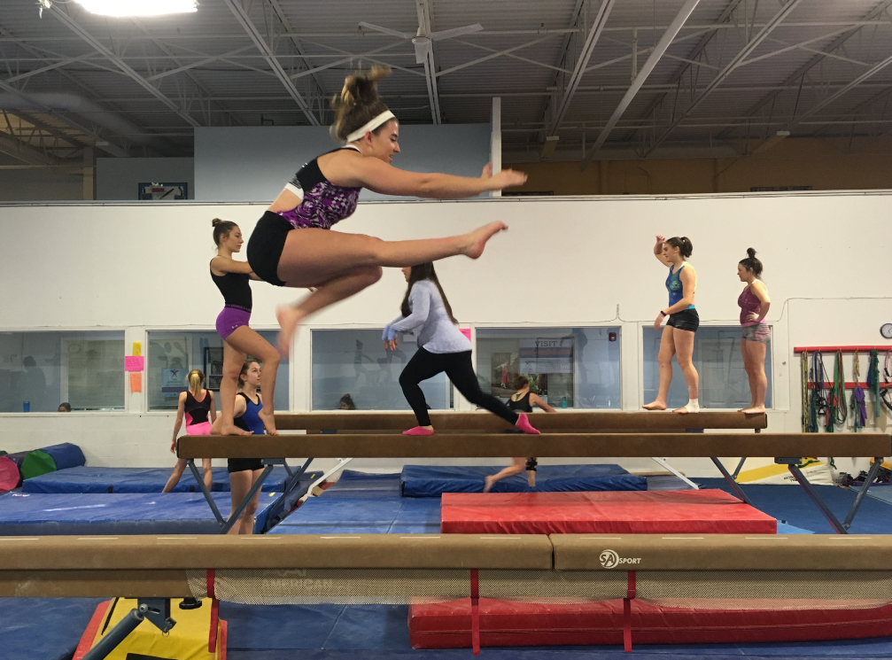 Krista Wohler, sophomore gymnast, practices a wolf jump on the beam at United States Gymnastics Training Center. The gymnastics team began practices at USGTC this past week.