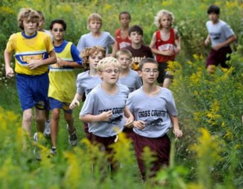 Seniors Patrick True (left) and Patrick Burns (right) shown here in a middle school cross country race, will be considered 12 sport athletes by the time they graduate after participating in three sports each of their four years throughout high school. Although the boys agree that being a part of the cross country, swim, and track teams is a time commitment, the two have no regrets and say it is all worth it.