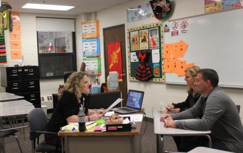 Carlye Hamilton, Spanish teacher, sits down with parents in her class to discuss their student's education.