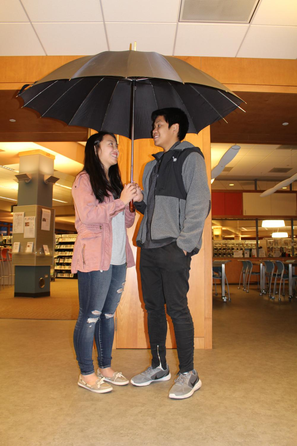 Matt Mauleon and Nicole Savage, senior couple, stands under an umbrella. Dating for over three years, the couple has battled the element of time throughout their long relationship.