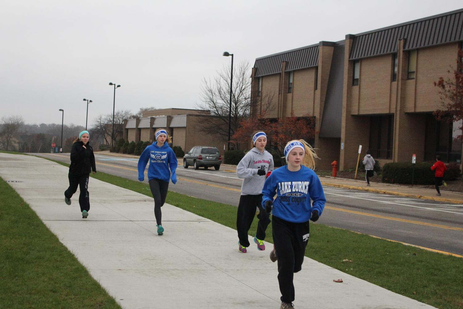 Hayley Burk, freshman, Emily Burns and Jillian Baffa, juniors, running after school for Polar Bears. Members of Polar Bears meet daily after school to train in the offseason.