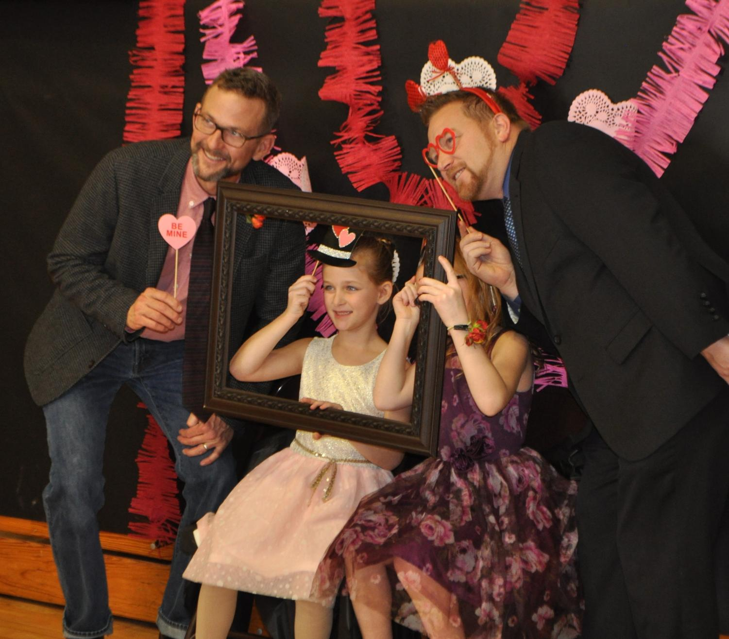 Fathers and daughters play dress up at the photo booth. This shows one of the activities at the dance, the photo booth. Families can dress up and take a silly photo by professional photographers.
