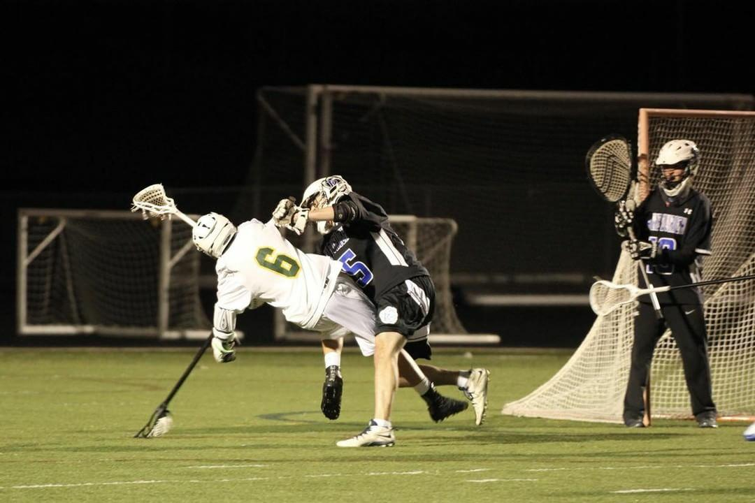 Jimmy Vaselopulos, senior, defends against an opposing player during a game. The LZHS Lacrosse Booster Club provides Vaselopulos and other players with more in-game experiences by helping pay for tournaments and matches.