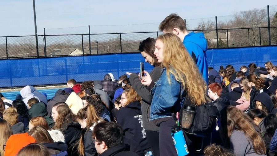 Julia Funk, senior, stands with other seniors among the sea of the students attending the walkout on March 14. At the school sanctioned, non political event, Funk and others passed out 'Our Opinions Matter,' and 'Enough is Enough,' signs to some students. Some people questioned if the signs fit the nonpolitical nature of the event.