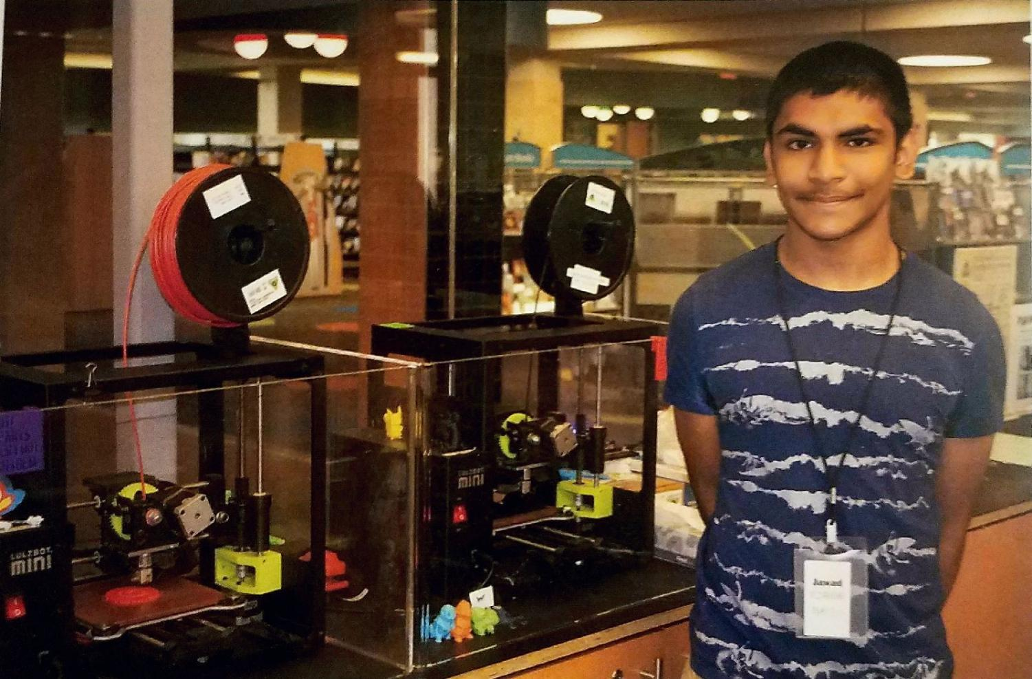 Jawad Alam, sophomore, stands in front of 3D printers at Ela Library. Alam was one of last summer's interns that the district made available for students.