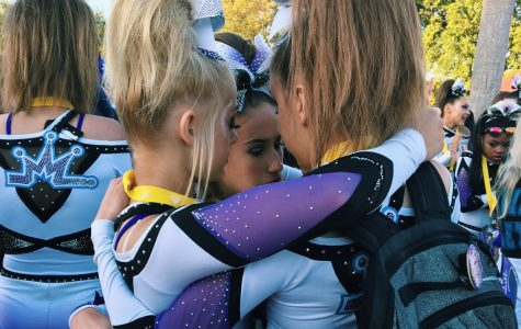 Elizabeth Russis, freshman, and her teammates share a hug after a successful competition. Teammates can offer different experiences as well, dynamics between girls on compeitive and highschool cheer can offer different experiences for cheerleaders.