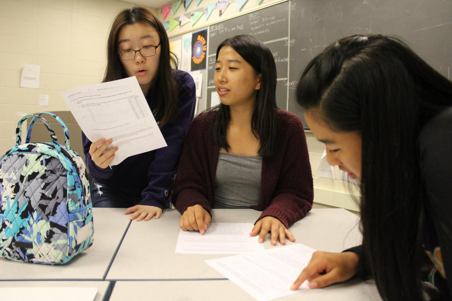 Sophomores Rachael Lee and Elizabeth Yen discuss their quiz corrections with Elizabeth's sister, Tiffany Yen. 5 underclassmen take AP Stats this year, breaking the norm, as it is a class typically taken by upperclassmen.