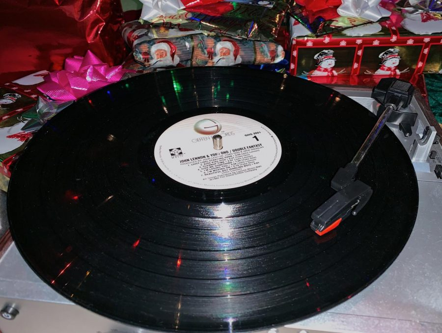 A record player spins a vinyl in front of Christmas presents. With these top 5 Christmas songs, any holiday occasion will feel special.