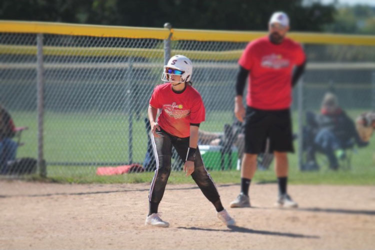 Waiting for the ball to be played, Kennedy Williams, who does club and school softball, sits on base. Her passion for softball has made her dedicated to the sport, deciding to do a club sport helps her gain experience and do what she loves.