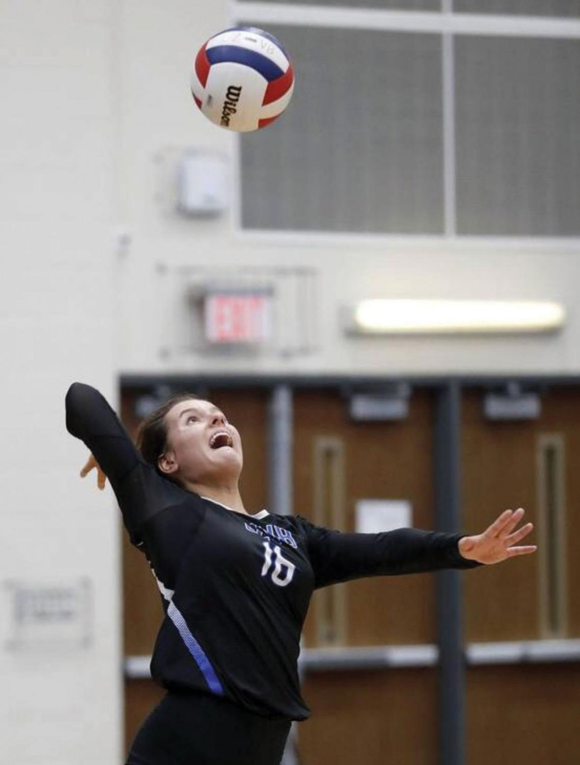 """Claudia Kieda, senior volleyball player and track runner, prepares to spike the ball during a volleyball match. Kieda says she enjoys being a multi-sport athlete because """"it's just fun to be involved in something constantly because each sport has a different season."""""""