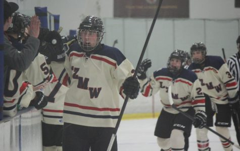 Players on the hockey team celebrate after a goal during a 4-3 shootout loss to Evanston on February 21. The team now is in the State Tournament and will play Wheaton on Sunday in the Sweet Sixteen