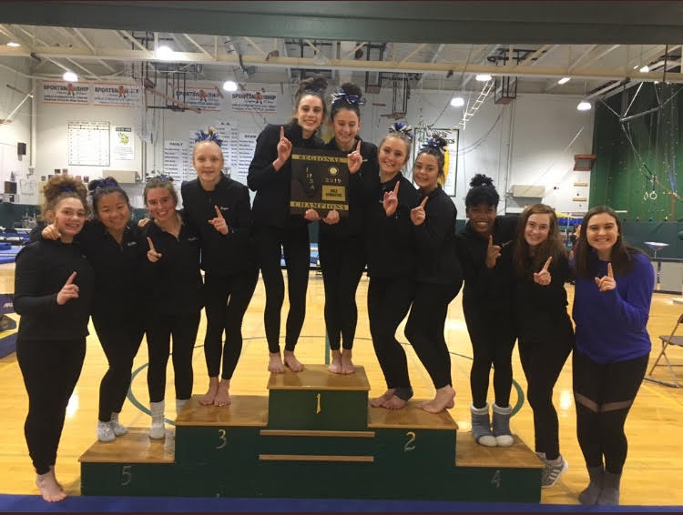 The gymnastics team poses with their Regional Championship hardware at Fremd High School on January 31. This victory ended Fremd's 26 year Regional Championship streak