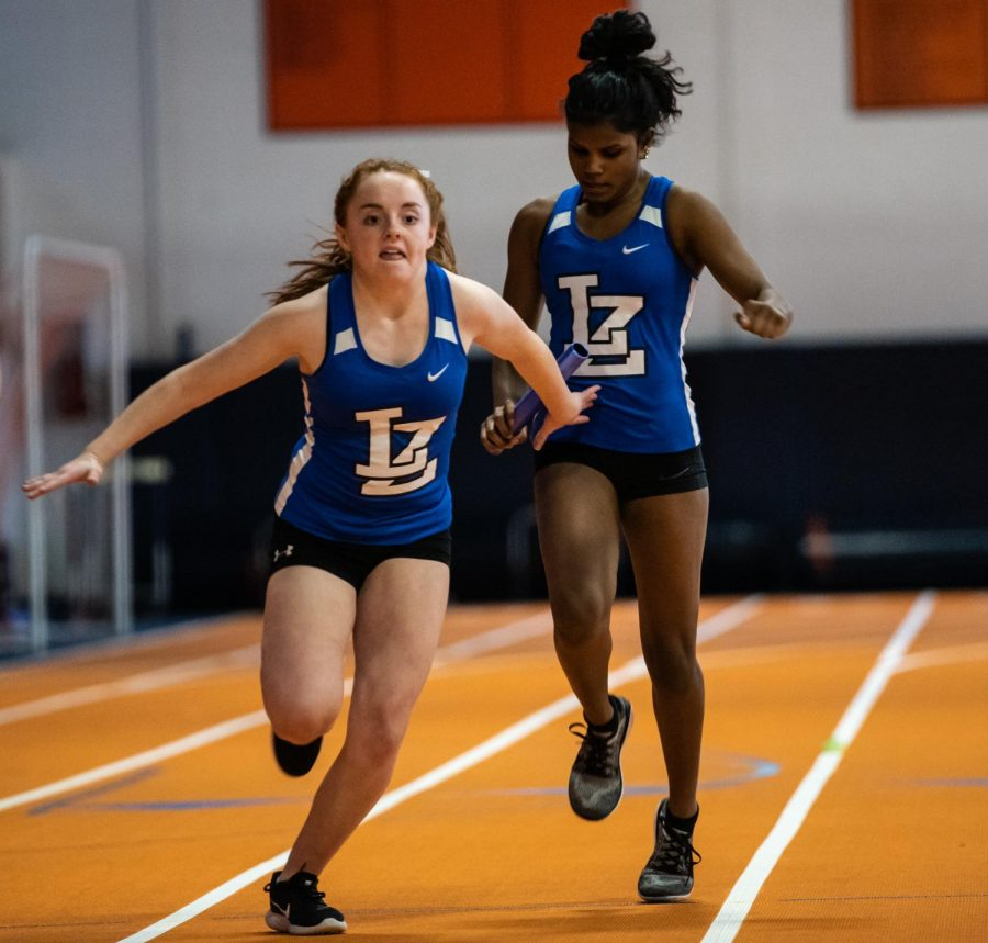 Rayna Kauffman, freshman, passes the baton to Cate Cillessen, freshman, in the Buffalo Grove Dual meet on Friday. The meet ended in a disappointing loss, but it was an improvement upon last year's score in the same meet