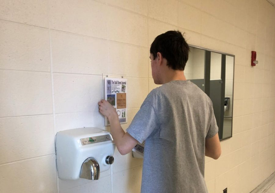 Andrew Koppel, transition student, posts a Stall Street Journal above the hand dryers. The students usually post the stall streets near the sinks as well as the stalls to promote good hygiene.