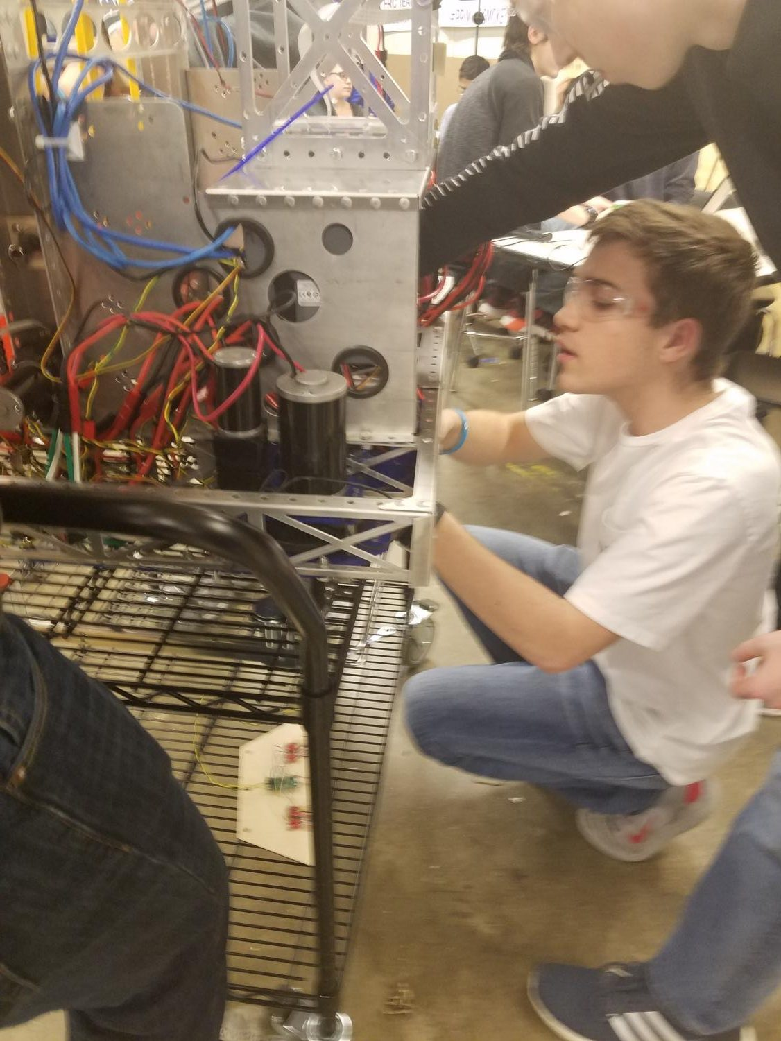 John McConnell, sophmore, is putting the finishing touches on the robot. Their upcoming competition is later next week.