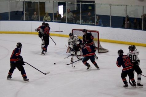 The hockey team attempts to deflect the puck away from their own net in a March 3 game against Wheaton. The game ended in a 5-0 loss, ending their season.