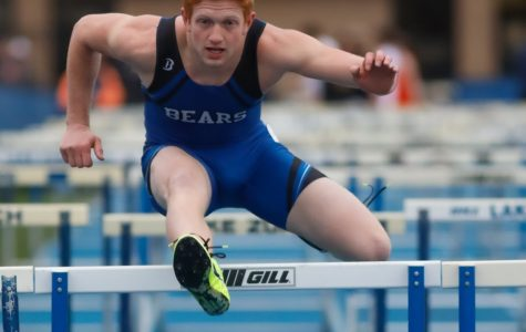 Marek Enters, senior, dashes over the hurdle in the 300 meter hurdles at the Bear Invite on Thursday. Enters came in third in the event.