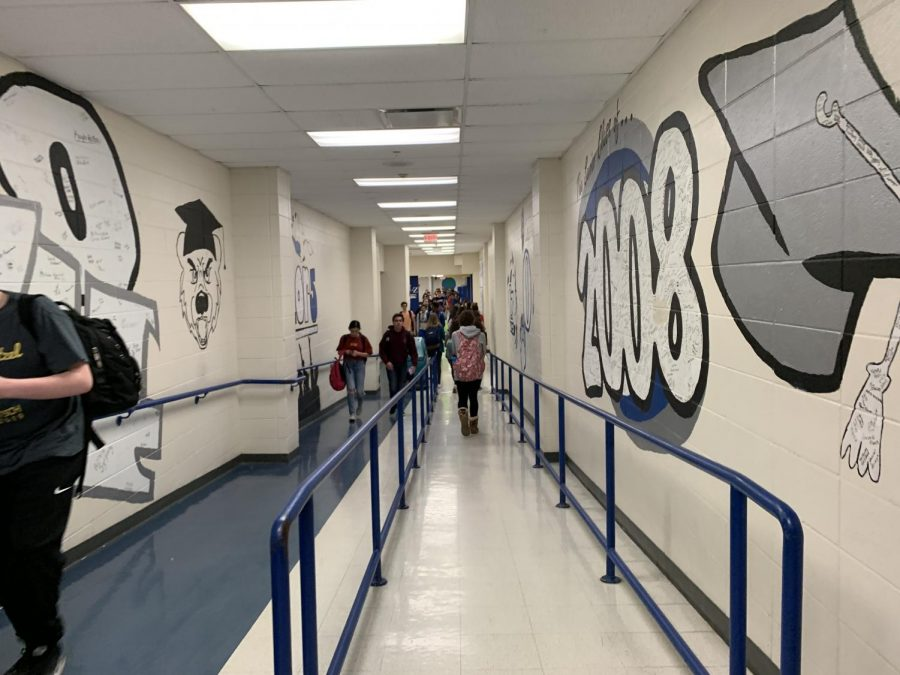 Students+walk+through+the+hallways+of+murals+with+signatures+of+past+seniors.+Kelly+Bush%2C+Senior%2C+sudjects+that+if+the+school+gives+students+prodjects+to+decorate+a+certain+area+of+the+school%2C+this+could+show+representation+and+liven+up+the+walls+of+the+school.+