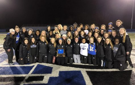 The girls track and field team poses with their NSC Championship trophy on Thursday at home. This is the team's second consecutive conference title.