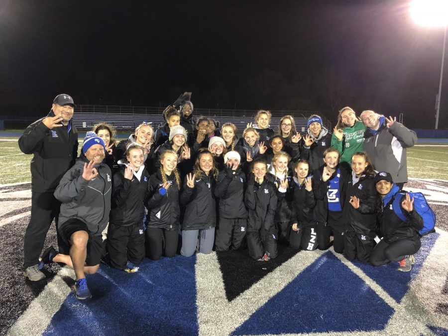 The girls track and field team poses while holding up the number three to signify their third-place finish at IHSA Sectionals on Thursday. The team will send seven envents to state next week as a result of their performance.