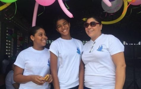 Gia Antoine, senior, standing with her aunt and cousin, who started a foundation for kids with mental and physical disabilities. At events like these, Antoine was able to help out those in Haiti through her volunteer work.